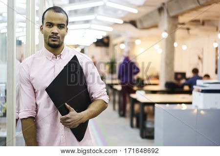 Portrait of handsome male executive of financial company organizing work of employee controlling fulfilling his tasks during working day standing on blurred indoor background in coworking office