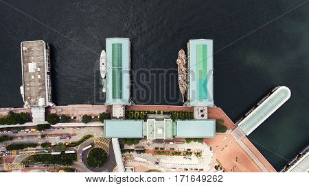 Top view aerial photo from flying drone of a yacht parking in developed China city with truck ships. Cityscape with modern buildings near road with cars and yacht parking in sea. Occupation Logistics