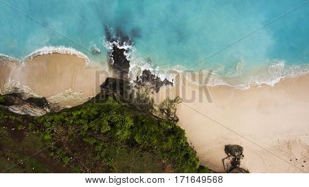 Top view aerial photo from flying drone of an amazing beauty nature landscape with sandy beach tropical trees and Indian Ocean with beautiful blue water.Perfect background for travel web site or blog