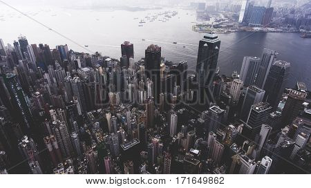 Aerial photo from flying drone of a modern China megapolis with tall skyscrapers with contemporary design near sea bay with riding luxury yachts. Developed Hong Kong city with business centers