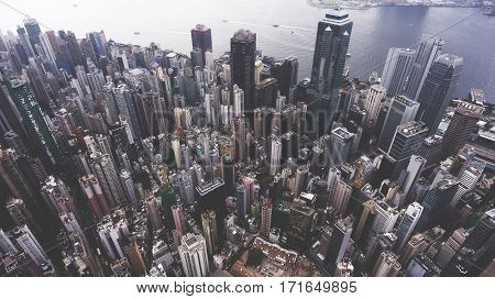 Top view aerial photo from flying drone of a developed metropolitan city in China with financial company. Hong Kong with office buildings and business centers near sea bay. Advanced infrastructure