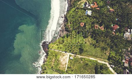 Aerial top view photo from drone of a paradise beach with tropical plants and blue calm sea. Beautiful nature b background. Amazing view on a Asian island with luxury hotels and rental villas near ocean