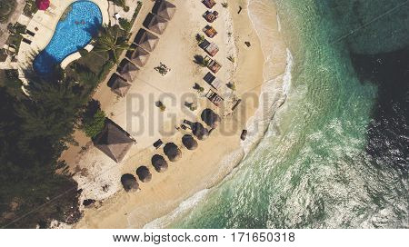 Top view aerial photo from drone of a beautiful view of seashore with luxury rental villas. Front beach hotel on tropical island in Thailand with turquoise blue water and coral bottom for snorkeling