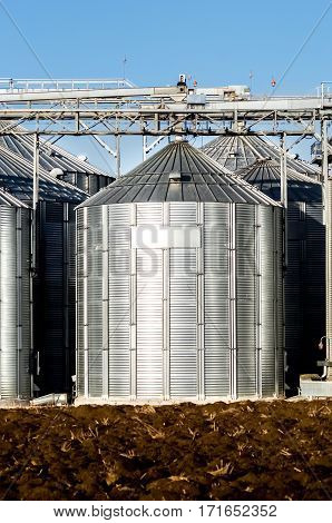 The complex silo installations for the storage of grain standing in the plowed field on a background of blue sky in winter