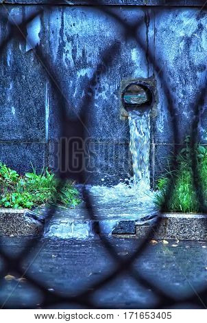 Pipe water rain. The flow of rainwater. Blurred silhouette of a metal fence.