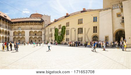 KRAKOW POLAND - MAY 16 2015: Tourists looking around inside central square of Wawel Royal Castle in Krakow Poland - May 16 2015