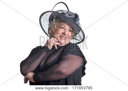 Senior woman in fur smiling on white background