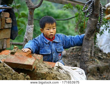 Wudanshan, China - Nov 1, 2007: Small Asian Boy At A Construction Site. According To Traditional  Be