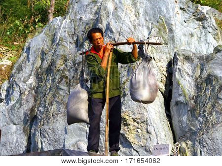 Wudang Shan, China - Nov 1, 2007: Man With Large Bales On The Steps In The Wudang Mountains. Most Mo