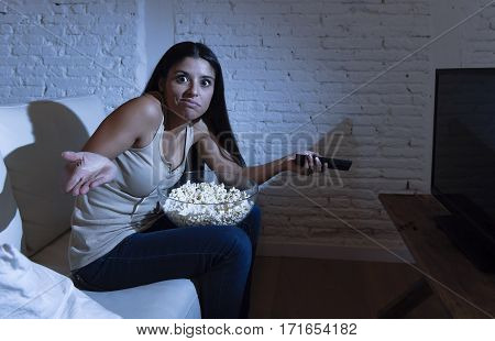 young beautiful hispanic woman lying at home sofa couch in living room watching television screaming desperate bored and disappointed about tv program in addiction concept