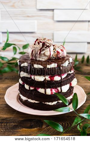 Black forest cake decorated with whipped cream, berry and chocolate sauce and meringues, selective focus