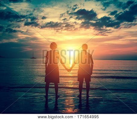 Silhouette of couple holding hands on the sea beach during sunset.