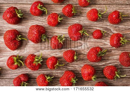 Texture of red ripe strawberries on wooden background. Summer ripe berries