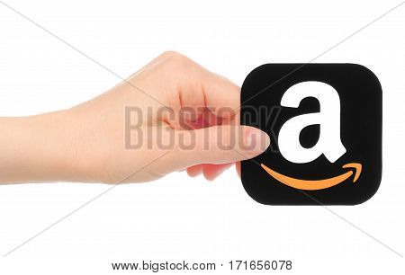 Kiev Ukraine - May 18 2016: Hand holds Amazon icon printed on paper. Amazon is an American electronic commerce company