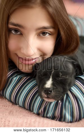 Young teenage girl lying with sleeping puppy dog. Clouseup portraite. Happy smiling girl holding her cute Staffordshire terrier puppy.