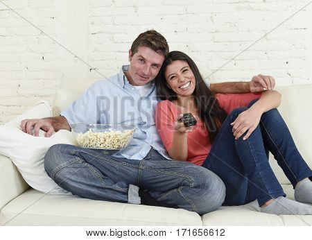 young happy attractive couple having fun at home enjoying watching television horror movie show or thriller film hugging nervous together scared in shock at home sofa couch terrified