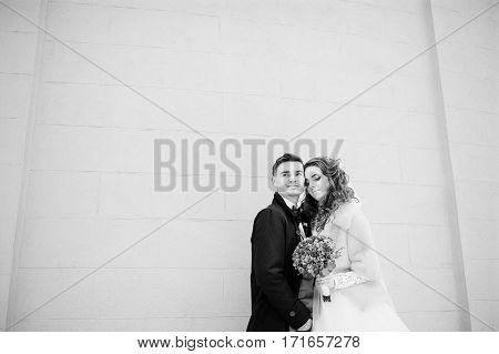 Young Wedding Couple At Cold Winter Day Against White Stone Wall Of Building. Black And White Photo.