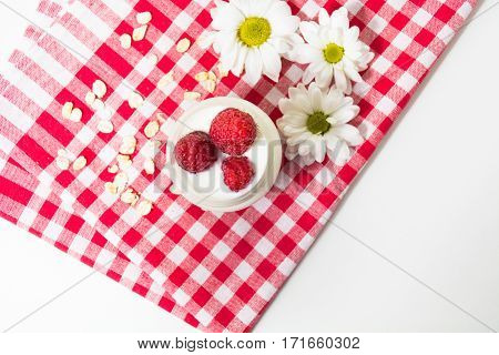 Overnight oatmeal with yogurt and raspberry on the checkered towel on the white background with copy space. Top view