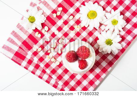Overnight oatmeal with yogurt and raspberry on the checkered towel on the white background. Top view