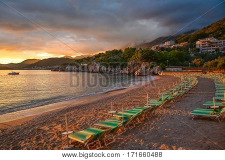 Rocky shore and loungers on the beach at sunset.