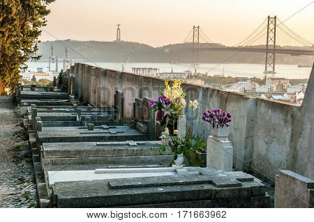Sunset in the Prazeres Cemetery, Lisbon. In the background the 25th of April Bridge and The Christ the King statue