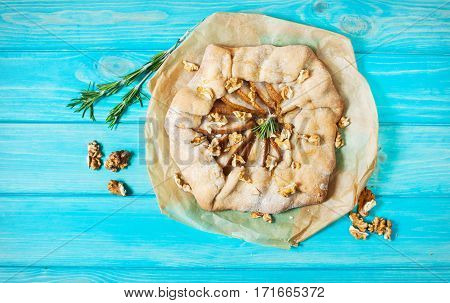 homemade cake with pears and walnuts on blue wood background.