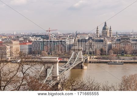 BUDAPEST HUNGARY - FEBRUARY 20 2016: View of the Szechenyi Chain Bridge over Danube River and church St. Stephen's Basilica in Budapest Hungary.