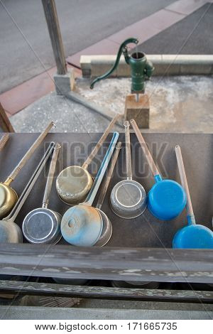 Multiple metal and plastic ladles on a table and a hand water pump next to a graveyard. Hand ladles are used as a part of Shinto ceremonies. Nobeoka Japan.