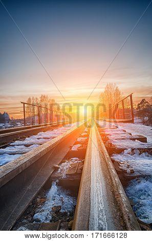 Sunset on the railway bridge. The glow of the sun