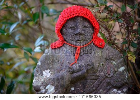 Close-up detail of a stone Jizo Bosatsu statue with a red knitted woollen cap. Travel and religion concept.