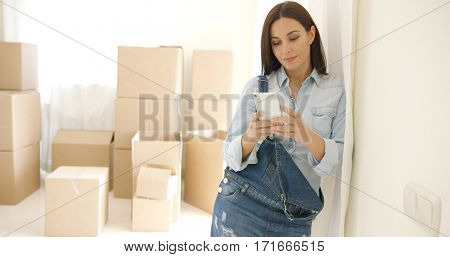 Young woman doing renovations checking messages