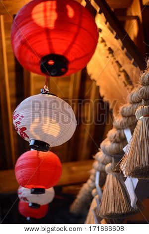 Close-up detail of multiple red and white paper lanterns hanging from the wooden ceiling of a Shinto shrine vertical orientation. Travel and architecture concept.