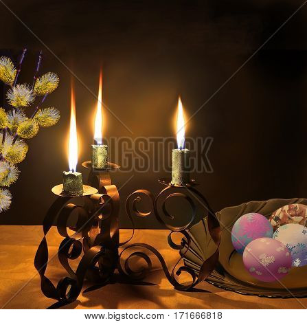 Easter night background and the symbols of the Great Resurrection of Jesus. Candlestick with three burning candles painted eggs and twigs of willow on the table with a tablecloth covered