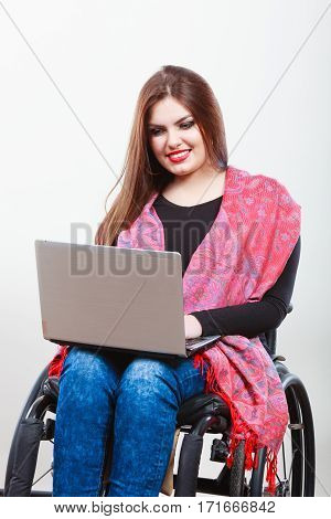 Disabled lady surfing on web. Young female on wheelchair using laptop. Internet technology education disability concept.
