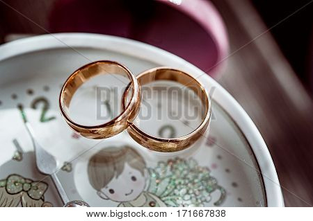 Macro Of Wedding Rings Next To The Flowers And Romantic Clock