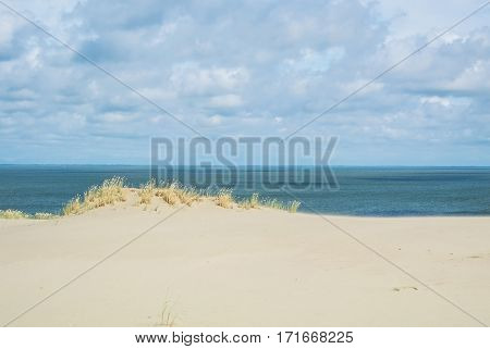 The sand shore and the sea under the clouds at Lithuania, Curonian Spit, Nida dune.