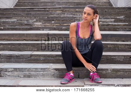 Fitness woman taking a break from running sitting on steps.