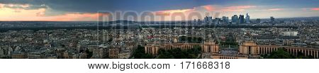 Evening panorama of Paris at sunset from a high tower. Large beautiful home on the horizon. The dark sky with a red sky at sunset. Night city with glowing street lamps.