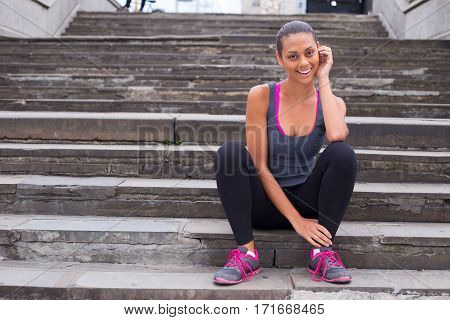 A happy girl sitting on steps relaxing after exercising