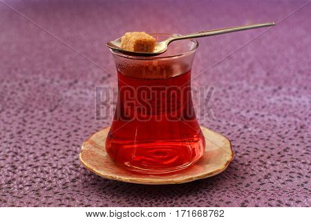 Oriental tea in traditional glass with one sugar cube