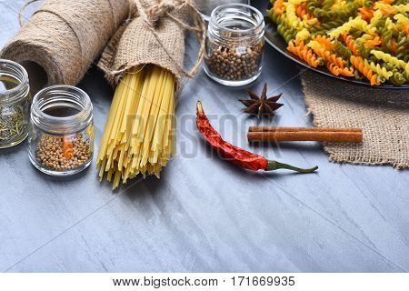 Bunch Of Spaghetti And Fusilli In Bowl With String Bobbin