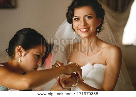 The smilling bride with bridesmaids in the room