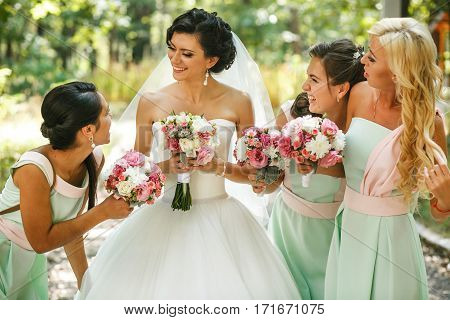 Elegant bridesmaids admiring of bride on the street