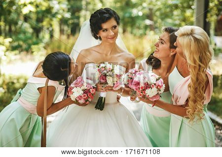 Beautiful bridesmaids admiring of bride on the street