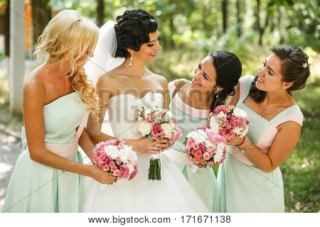 Bridesmaids admiring of bride on the street