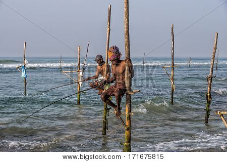 Weligama, Sri Lanka - January 11 2017: Unidentified Local Fishermen Are Fishing In Unique Style. Thi
