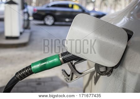 To fill the machine with fuel. Mashunya fill with gasoline at a gas station. Gas station pump. Man filling gasoline fuel in car holding nozzle. Close up.