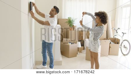 Young couple hanging pictures in their new home