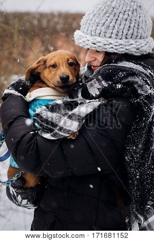 Stylish Hipster Woman Holding With Cute Puppy In Snowy Cold Winter Park And Caress. Moments Of True