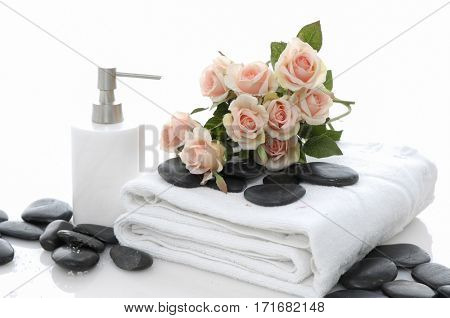 Pile of black stones ,oil and rose on towel –white background